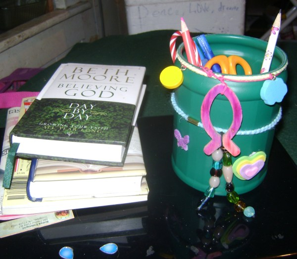 Teal bucket with hair ties and beads attached on a desk next to some books