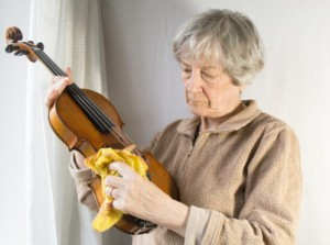 A woman dusting her violin.