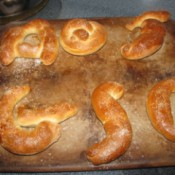A batch of soft pretzels in letter shapes.