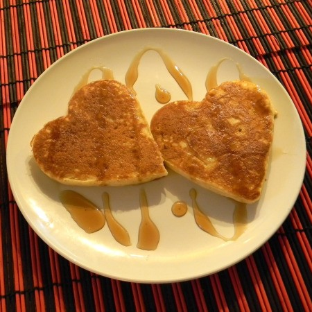 Two heart shaped pancakse on a plate with syrup drizzled over them.
