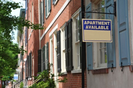 "An street with an ""Apartment For Rent"" sign."