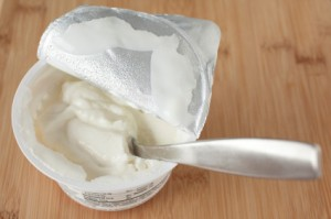 Uses for Yogurt Containers, Open Yogurt Container With spoon in it.