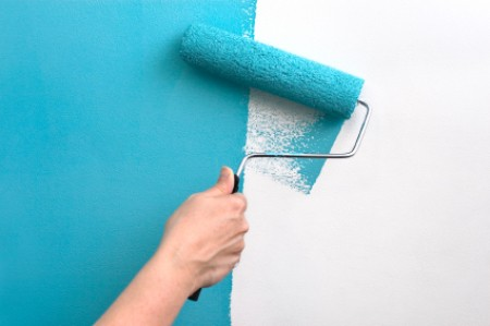 Paint Roller Putting Teal Paint on Wall