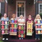 Five women holding finished Mason jar quilts.