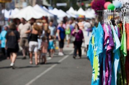 A street fair with tie dyed t-shirts for sale.