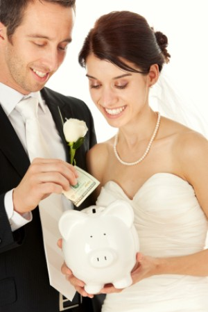 Bride and Groom Putting Money in Piggy Bank