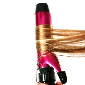 Someone curling hair with a pink and black curling iron.