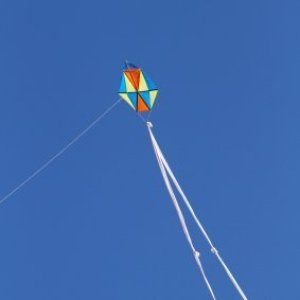 Homemade kite with long double tail against the sky.