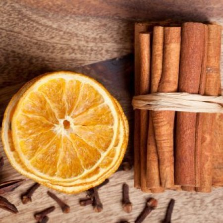 Dried orange slices, bundle of cinnamon sticks, and cloves.