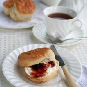 Scone on a plate with tea cup and saucer off to upper right.