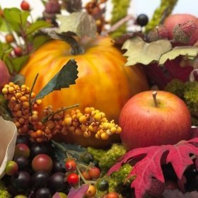 Autumn leaves, pumpkin, apple, and other elements of a fall centerpiece.