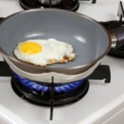 Egg frying in Teflon pan on gas stove.