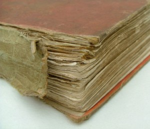 A worn and torn binding of a hard cover book.