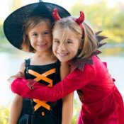 Two girls in a witch and devil costumes.
