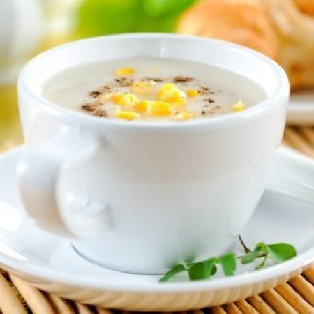 Cup of corn chowder with cheese and bacon on it.