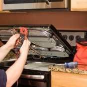 Repairman working on a stove.