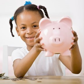Young girl holding up a pink piggy bank