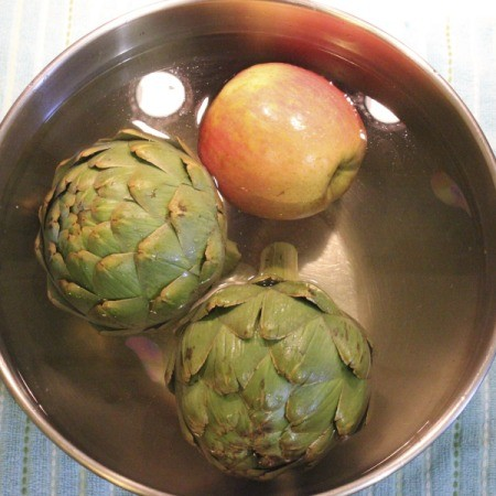 Bowl containing two artichokes and an apple in veggie wash.