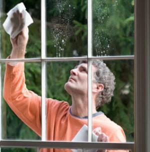 A man cleaning a window in his house.