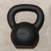 One 26 pound (12 kg) black kettlebell used for exercising.