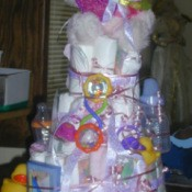 Very tall diaper cake with a white teddy bear on top.