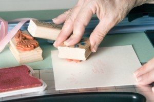 A crafter using rubber stamps to decorate a handmade card.