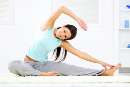 A woman stretching or doing yoga at home.