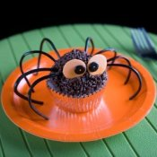 A cupcake decorated to look like a black spider.