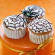 Cupcakes with spiderweb designs on top.