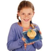 Girl holding a cupcake decorated like a pumpkin.