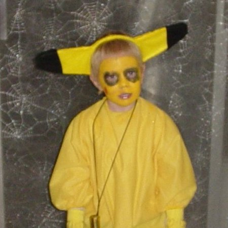 Boy in Pikachu Costume Against Spider Web Curtain Background
