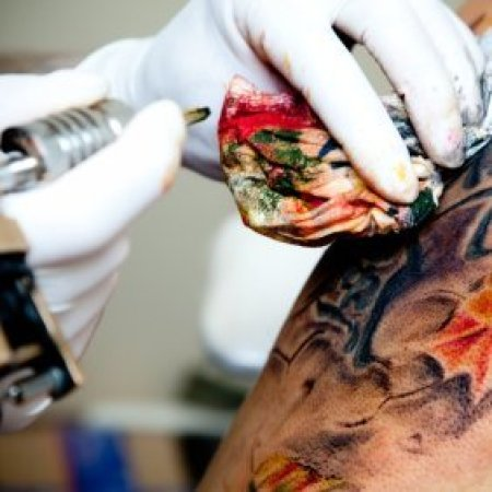 A tattoo artist working on a tattoo.