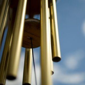 Upclose photo of a wind chime hanging outside.