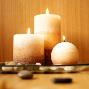 Pillar candles on a glass plate with river rocks.
