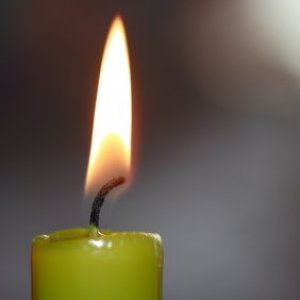 A green candle that is burning.