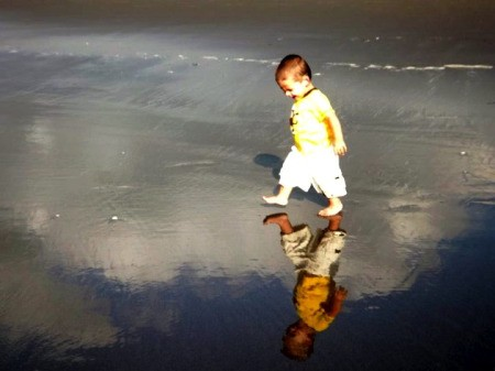 Boy walking on the Beach looking at his reflection