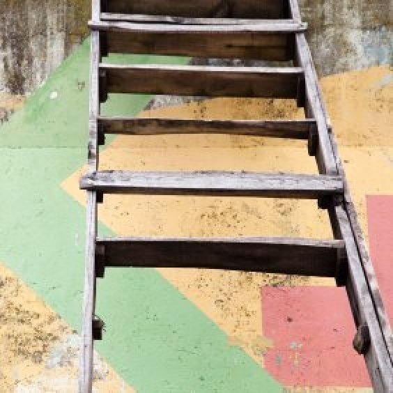 Old wooden ladder leaning against a concrete wall with painted designs.