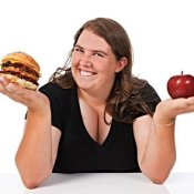 Woman choosing between an apple and a hamburger.