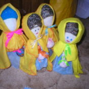 Small dolls with yellow capes made from cloths.