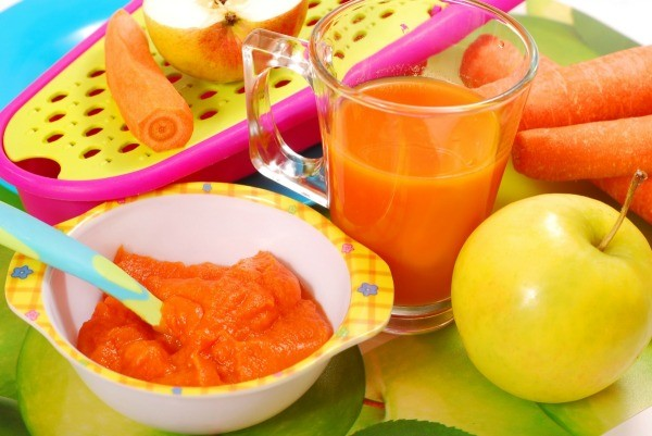 Dish of homemade carrot baby food. It is surrounded by fresh carrots and a ceramic bunny.