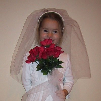 Young girl in a bride costume with red roses.