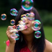 Young woman blowing bubbles.