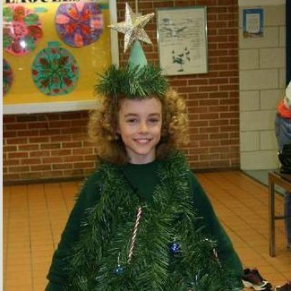 Young girl in a Christmas tree costume.