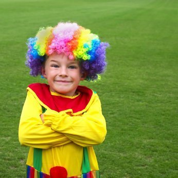 Child in a brightly colored clown costume.