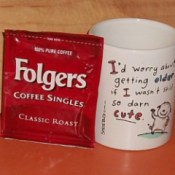 Package of Folger's Singles next to a coffee cup.