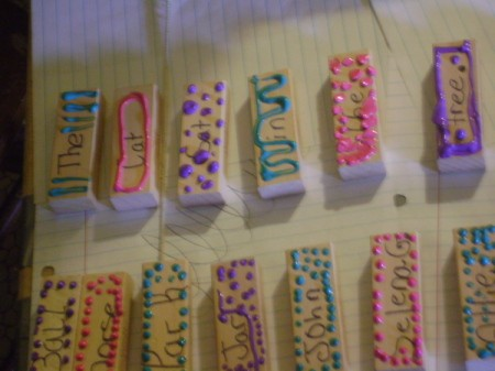 Closeup of decorated Jenga sticks with words added.