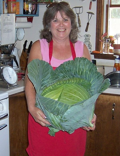 Photo of a woman holding a huge cabbage.