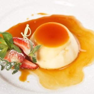 Panna cotta with caramel sauce and fresh strawberries.