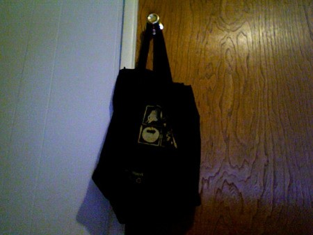 Book bag hanging on the knob on back of door.