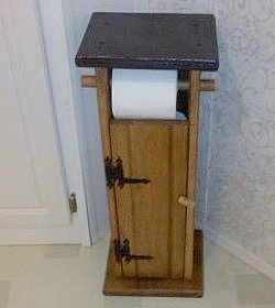A bathroom toilet paper holder that is built like an outhouse.
